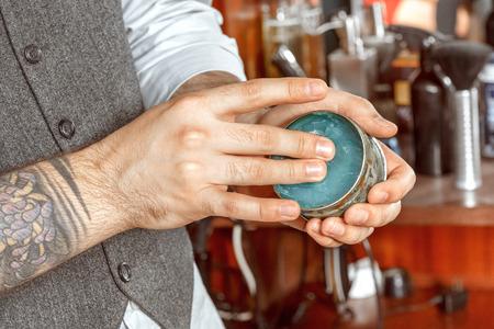 close up of barbers hand and a gel jar Standard-Bild