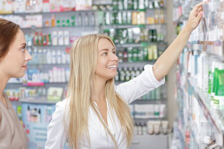 druggist: Beautiful girl druggist helping a customer Stock Photo