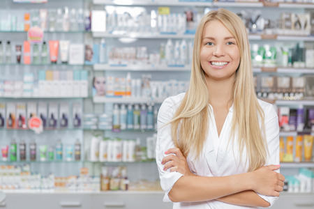 Young beautiful pharmacist standing in a drugstore