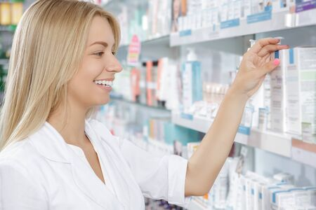 druggist: Beautiful pharmacist choosing the product in drugstore