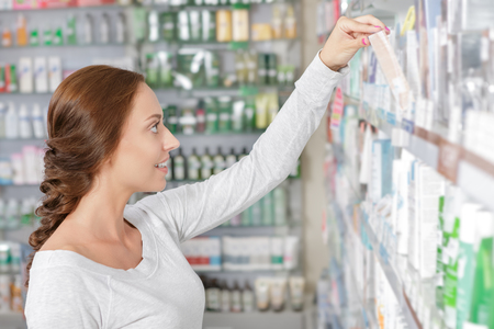 Beautiful young woman making decision in drugstore