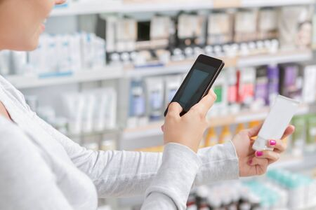 mobile shop: Close up of a woman taking picture of the product in drugstore