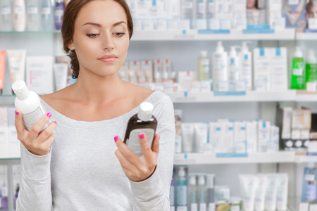 can't: Beautiful girl cant decide what to buy in drugstore Stock Photo