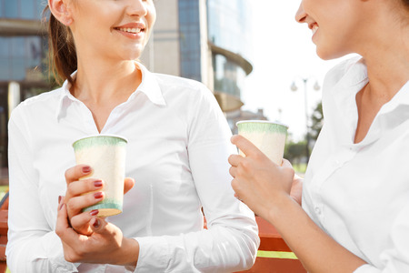 coffeebreak: Two attractive businesswoman talking during coffeebreak outdoors Stock Photo
