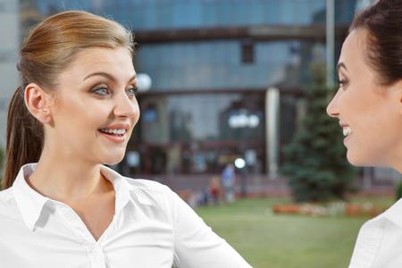 amigas conversando: Dos empresarias de tener una conversación amistosa al aire libre