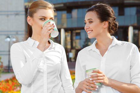 coffeebreak: Two beautiful businesswoman having a coffeebreak outdoors