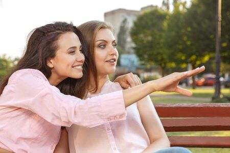 attractive people: Two beautiful women sitting on the bench Stock Photo