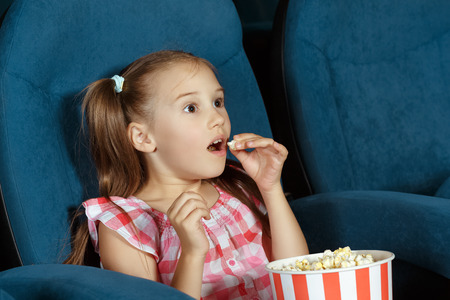 Adorable little girl watching movie with delight Standard-Bild