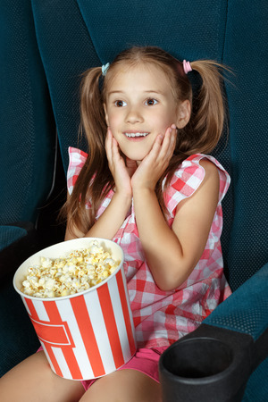 Pretty little girl watching movie at the cinema