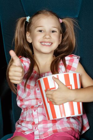 funny face: Little girl showing thumbs up at the cinema Stock Photo