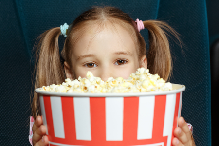 pretty hair: Adorable little girl with popcorn at the cinema Stock Photo