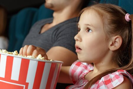Adorable little girl with popcorn at the cinema 版權商用圖片