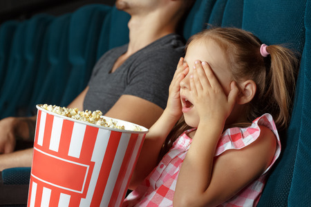 sitting pretty: Little girl closing her eyes with hands at the cinema Stock Photo