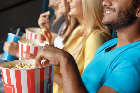 Vrienden eten van popcorn in de bioscoop Stockfoto
