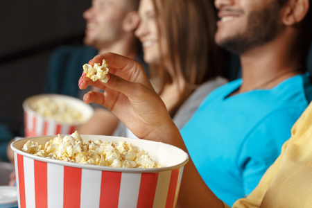 eating popcorn: Group of people eating popcorn in the cinema