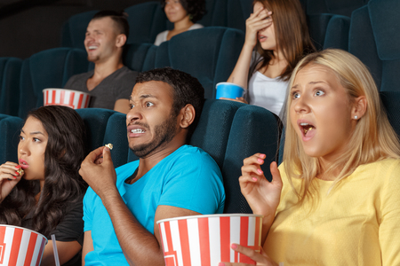 Friends watching horror film at the cinema