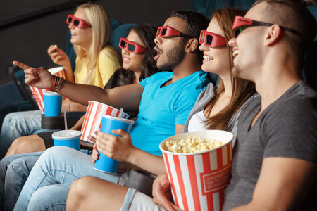 friends talking: Happy friends holding a refreshment and popcorn in the cinema Stock Photo