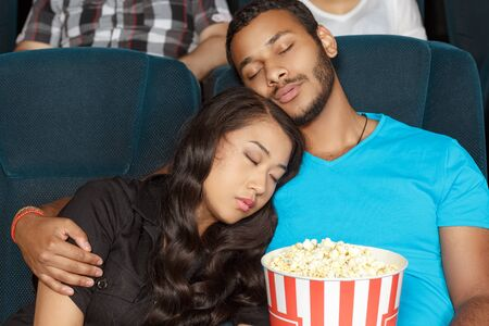 somnolence: Young couple going asleep during the movie
