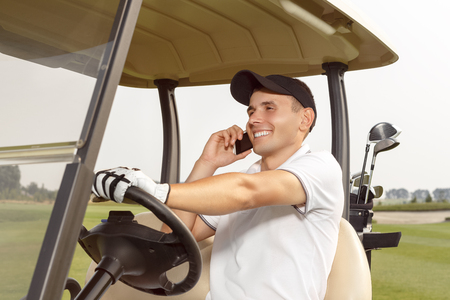 Man sitting in a golf cart and talking on his cellphone