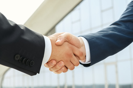 business hand shake: Powerful partnership supported by a handshake outdoors