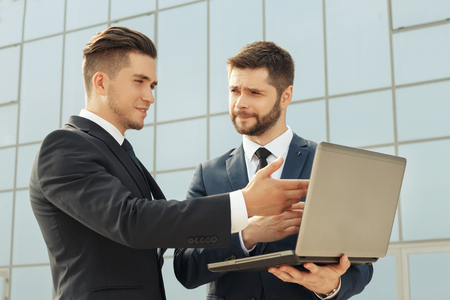 office wear: Two businessmen using laptop while having a meeting