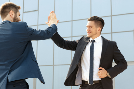 high view: Two handsome business colleagues high fiving outdoors