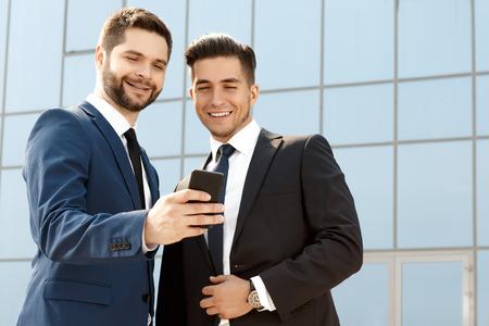 ejecutivo en oficina: Dos colegas que discuten algo en un tel�fono celular