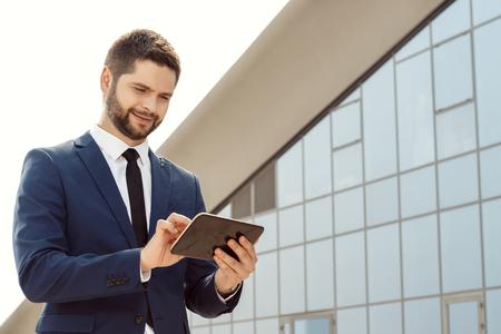 Young businessman using a digital tablet outdoors Standard-Bild