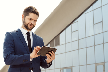 tablets: Young businessman using a digital tablet outdoors Stock Photo