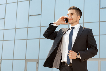 young executive: Handsome businessman talking on his cellphone outdoors