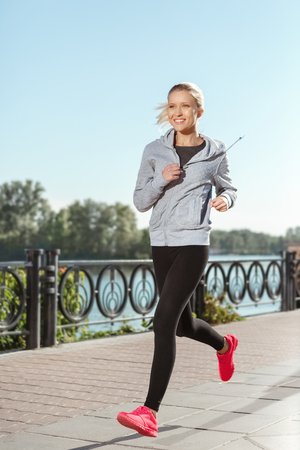run out: Attractive young girl running  along the waterfront Stock Photo