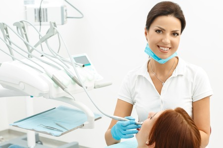 Female attracrtive dentist and her patient in dental office