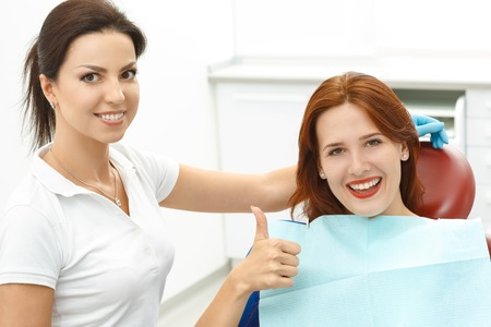 dental surgeon: Girl sitting in a dentists chair giving a thumbs up Stock Photo
