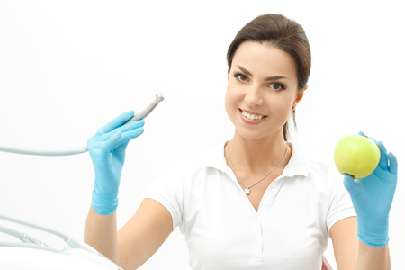 breath: Attractive dentist holding an apple and smiling to camera