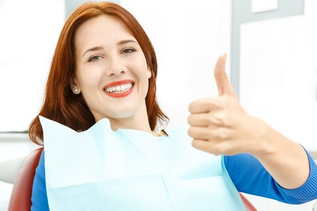 dentistry: Girl sitting in a dentists chair giving a thumbs up Stock Photo