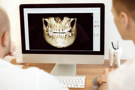 dentista: Los dentistas y asistente en discusiones sobre la fotograf�a de rayos x en el ordenador