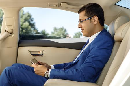 asiento coche: Joven empresario sentado en el asiento trasero de un coche, con su tableta digital