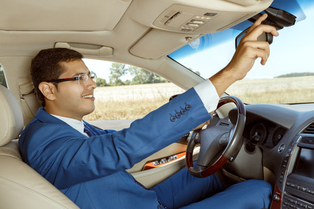 mirror: Businessman adjusting the rearview mirror while driving a car Stock Photo