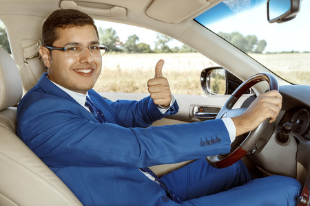 drivers seat: Businessman showing a thumbs up while sitting in the drivers seat