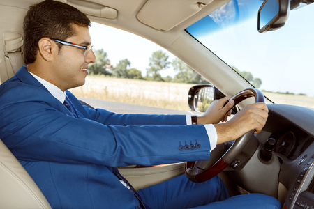transport interior: Young handsome businessman driving his new car Stock Photo