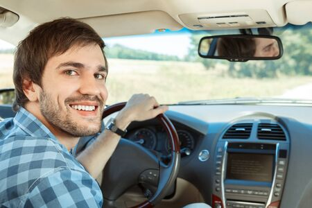 hombres jovenes: Hombre joven que sonríe a la cámara en el coche