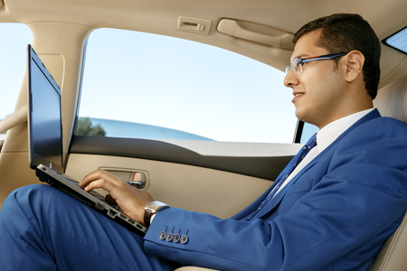 Young businessman sitting in the back-seat of a car, using his laptop