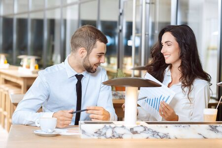 woman window: Two business partners discussing diagram report during coffee break Stock Photo