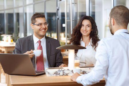 amigas conversando: Tres colegas de negocios tener una conversación amistosa durante la pausa para el café