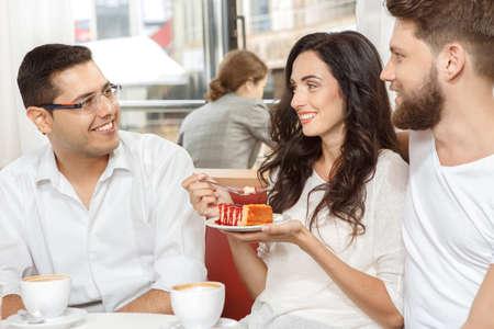 amigas conversando: Tres amigos en el caf� con una conversaci�n amistosa