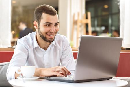 mecanografía: apuesto hombre de negocios usando la computadora portátil durante la pausa para el café en el café