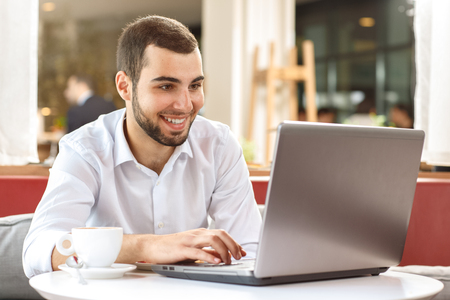 Handsome businessman using laptop during coffee break in cafe