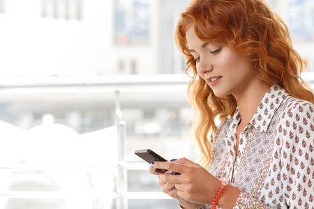 fille sexy: Attractive fille aux cheveux rouges en utilisant smartphone dans un caf�