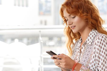 sitting pretty: Attractive red-haired girl using smartphone in cafe
