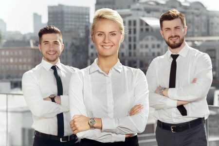 カメラに笑顔のオフィスビルの近くの 3 つの自信を持ってビジネス パートナー 写真素材